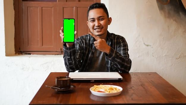 Азиатский деловой человек играет в телефон с зеленым экраном в кафе