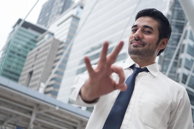 大丈夫ジェスチャーを指しているアジアのビジネスマン。アジアの、北インドの成功した自信のあるビジネスマンの肖像画は、彼の承認、はい、okまたはokの手のサインを指します