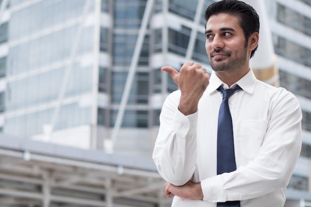 親指を上に向けるジェスチャーを指すアジアのビジネスマン。アジアの、北インドの成功した自信のあるビジネスマンの肖像画は、彼の承認を示しています、はい、大丈夫です