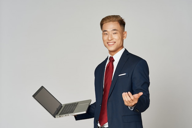 Asian business man posing in suit in  on a colored space