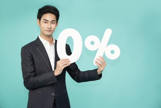 Азиатский деловой человек показывает и держит номер 0, изолированные на зеленом фоне