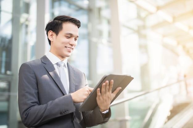 아시아 사업가가 노트북 수표를 사용하는 동안 프론트 오피스에 서서 미소를 짓고 있다