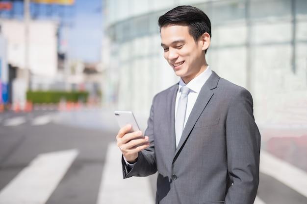 아시아 사업가는 터치스크린으로 스마트폰을 사용하는 동안 프론트 오피스에 서서 웃고 있다