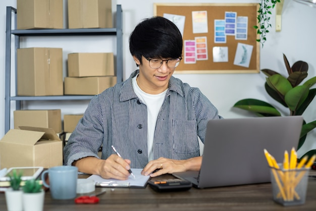 아시아 비즈니스 남자 시작 중소 기업가 또는 골판지 상자에서 일하는 프리랜서 고객, 온라인 판매, 전자 상거래, 포장 및 배송 개념 배달 상자를 준비합니다.