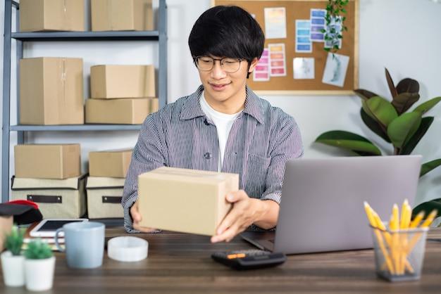 Азиатский деловой человек, начинающий предприниматель малого и среднего бизнеса или внештатный работник, работающий в картонной коробке, готовит коробку для доставки для клиента, онлайн-продажи, электронную коммерцию, упаковку и концепцию доставки.