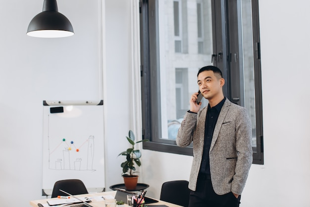 Asian business man talking on mobile phone in modern loft office