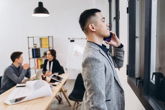 モダンなロフトオフィスで携帯電話で話しているアジアビジネスの男性