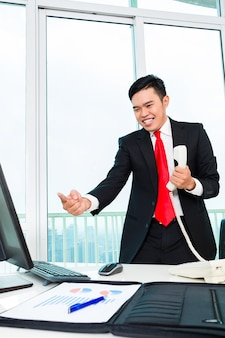 Asian business man telephoning in office controlling profit