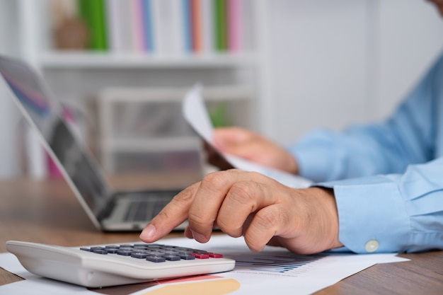 아시아 사업가 계산기를 사용하여 손익에 대한 수입과 지출을 계산합니다.