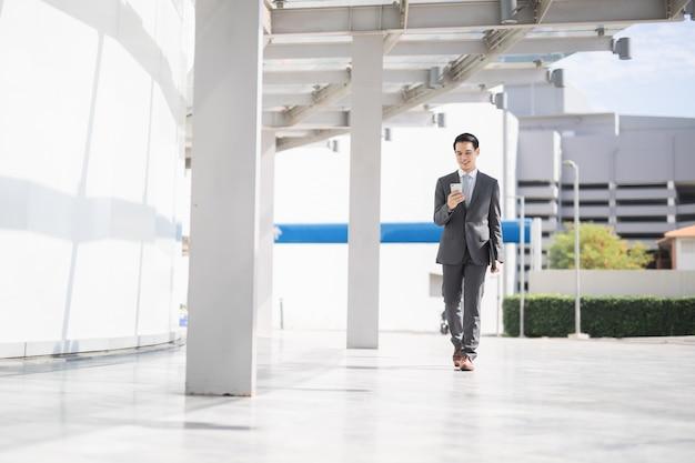 아시아 비즈니스 사람이 공항에서 내부 산책을 여행하는 스마트 폰을 사용합니다.