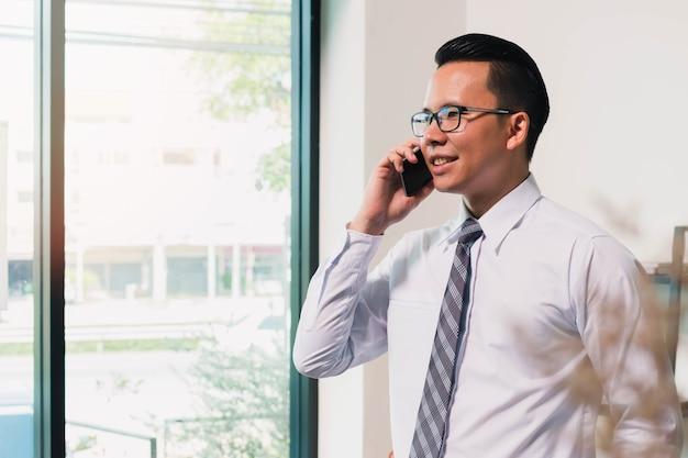 自宅のオフィスの背景でスマートフォンを使用しているアジアのビジネスマン