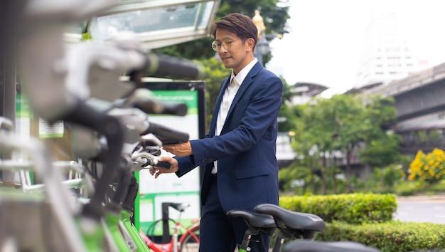 屋外で公共の自転車を借りるためにスマートフォンを使用しているアジアのビジネスマン。都市環境でのレンタル自転車。