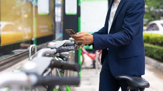Asian business man using smartphone for  rent public bicycle outdoors. bicycles for rent in city environment.