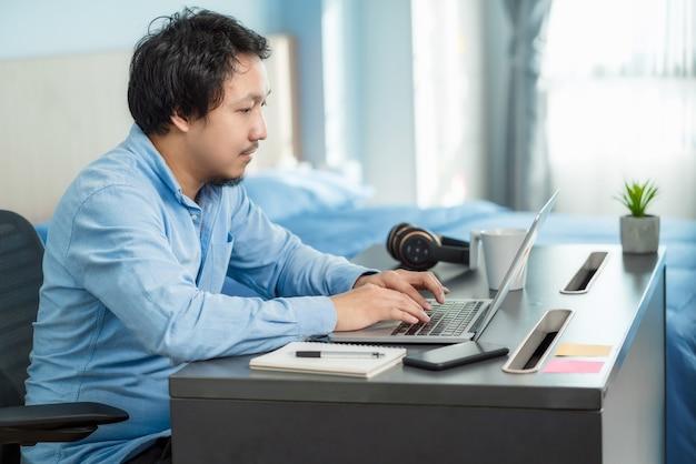 기술 노트북을 사용하고 집에서 실내 침실에서 일하는 아시아 사업가