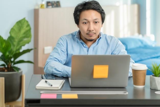 Азиатский деловой человек, использующий технологический ноутбук и работающий из дома с неожиданным действием в спальне