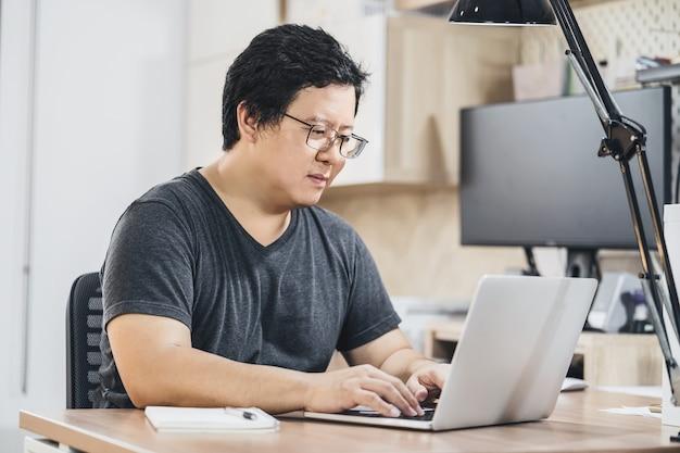 Азиатский деловой человек, использующий технологический ноутбук для работы из дома в спальне