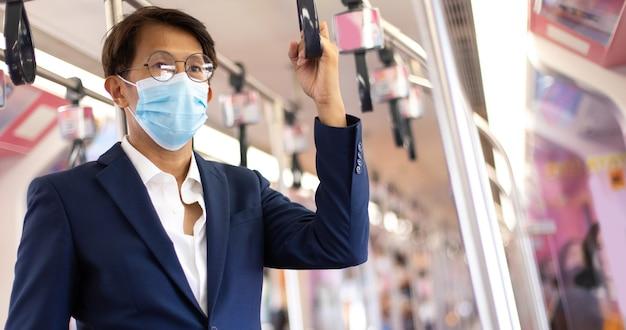 Covid-19 전염병 동안 대중 교통으로 통근하는 동안 얼굴 마스크를 쓴 아시아 사업가.