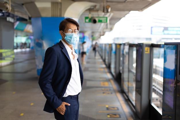 Covid-19 전염병 동안 대중 교통 역으로 통근하는 동안 얼굴 마스크를 쓴 아시아 사업가.