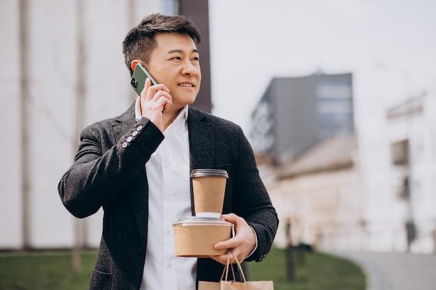 電話で話して、食べ物を持ち帰るアジアのビジネスマン