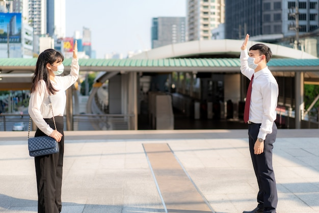 Asian business man and woman greet and say hello with business colleague and wearing mask standing distance of 1 meter distance protect from covid-19 viruses