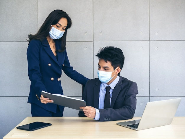 Asian business man and woman wearing suit and protective face masks look at report chart