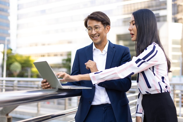 Asian business man and woman working on laptop computer standing outside office building.