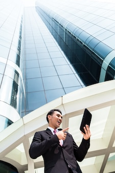 Asian business man working outside on tablet pc