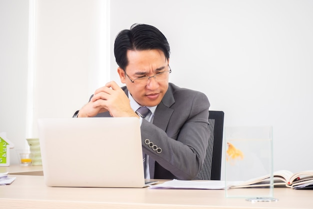 Asian business man in working room. serious and thinking action.