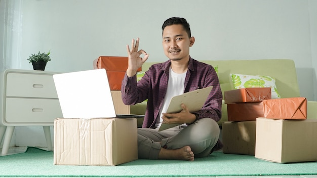 Asian business man working using laptop gesturing clear at home