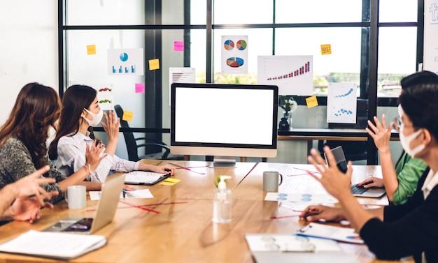 白いモックアップ空白の画面でデスクトップコンピュータとアジアのビジネス会議
