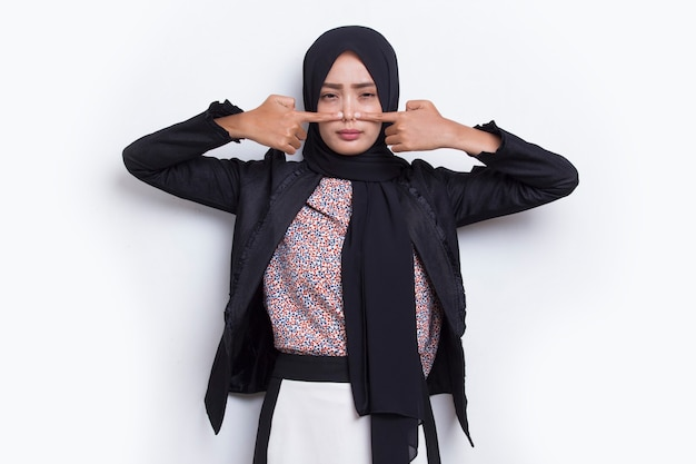 Asian business muslim woman holding her nose because of a bad smell