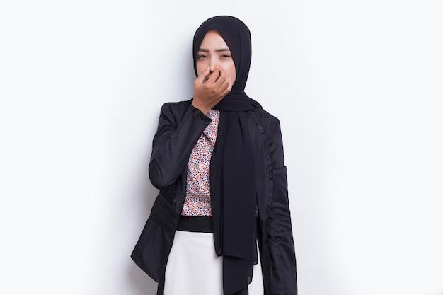 나쁜 냄새 때문에 코를 잡고 있는 아시아 비즈니스 이슬람 여성