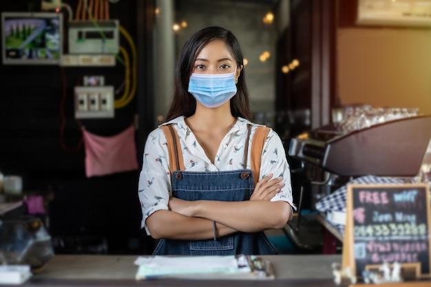 아시아 비즈니스 소유자와 바리 스타가 얼굴 마스크를 쓰고 커피 숍을 재개 한 후 웃고