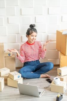 Азиатский владелец бизнеса работая дома с коробкой упаковки на рабочем месте