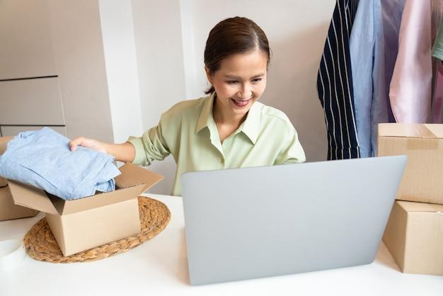 그녀의 온라인 상점의 포장 상자와 함께 집에서 일하는 아시아 비즈니스 소유자는 알파 세대 라이프 스타일 개념 인 고객에게 제품을 제공 할 준비를합니다.