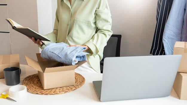 彼女のオンラインストアのパッキングボックスで在宅勤務しているアジアのビジネスオーナーは、アルファ世代のライフスタイルコンセプトである顧客に製品を届ける準備をしています。