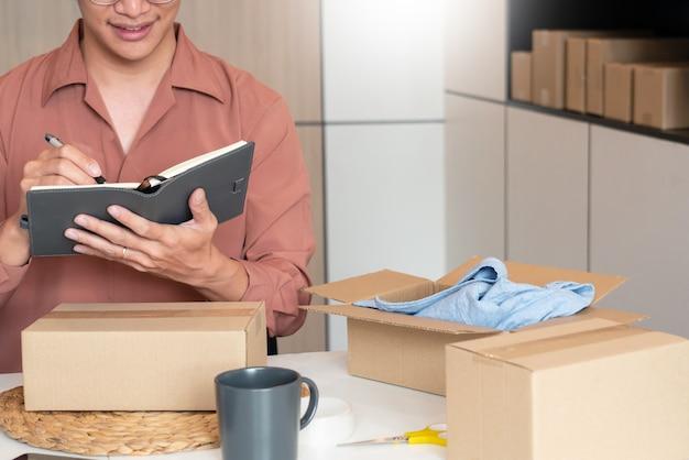 그의 온라인 상점의 포장 상자를 가지고 집에서 일하는 아시아 비즈니스 소유자는 알파 세대 라이프 스타일 개념 인 고객에게 제품을 제공 할 준비를합니다.