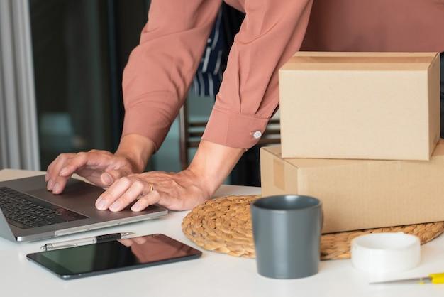 Азиатский владелец бизнеса, работающий дома с упаковочной коробкой своего интернет-магазина, готовится доставлять продукты клиентам, концепция стиля жизни альфа-поколения.