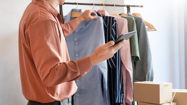 彼のオンラインストアの梱包箱を持って在宅勤務しているアジアのビジネスオーナーは、顧客に製品を届ける準備をしています