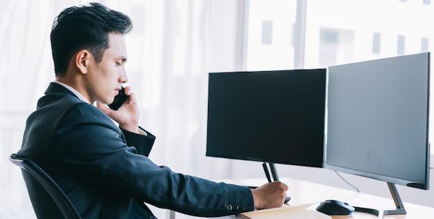 아시아 사업가들은 전화로 작업하는 데 집중하고 있습니다. 빈 화면이 두 개인 컴퓨터