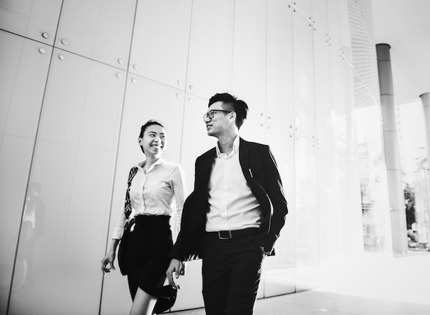 Asian business people in a disussion while walking