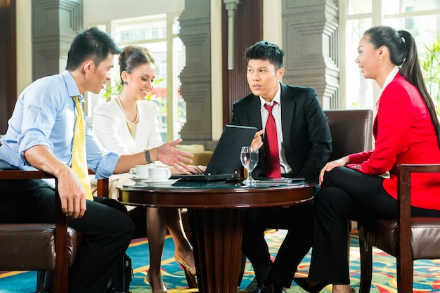 Asian business people at meeting in hotel lobby