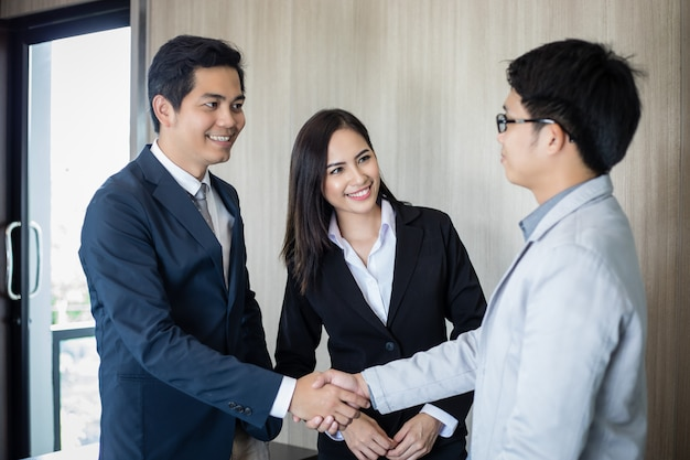 Asian business people shaking hands and smiling their agreement to sign contract and finishing up a meeting