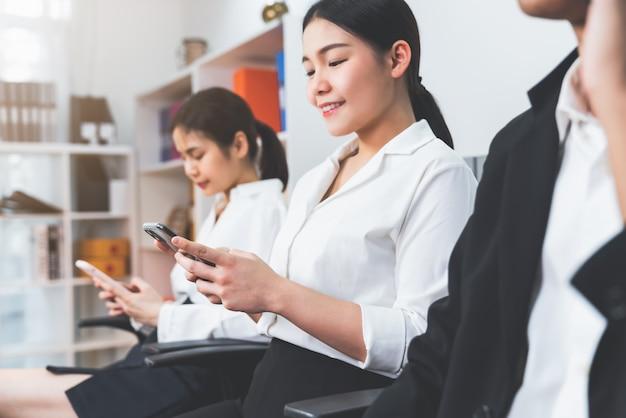 Азиатские бизнесмены сидя на стуле на офисе используя smartphone и контакт с клиентами. концепция работы в команде.
