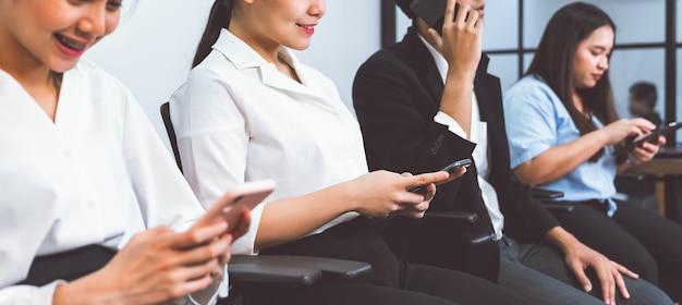 スマートフォンを使用してオフィスの椅子に座って顧客と接触するアジアのビジネスマン。