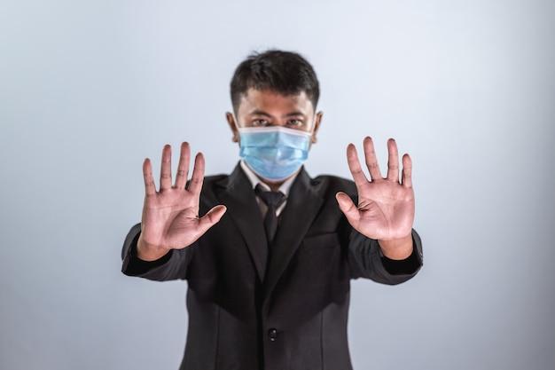 アジアのビジネスマンは、コロナウイルス病を予防するためにマスクを着用し、コロナウイルスを阻止するために手のサインを表示します。