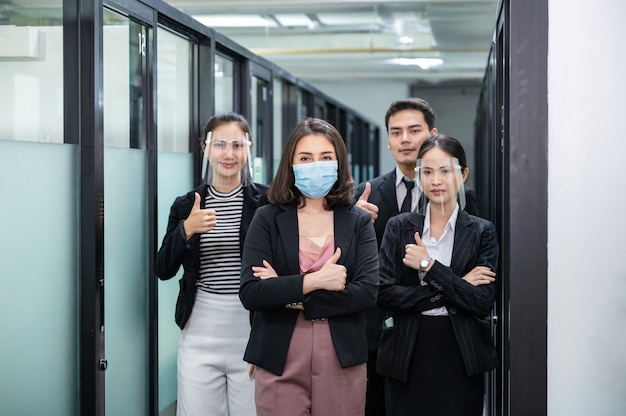 Asian business people wearing face mask, face shield with showing thumbs up in reopen office