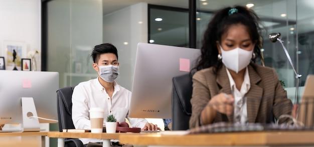保護マスクを身に着けているオフィスで働くアジアのビジネスパーソン