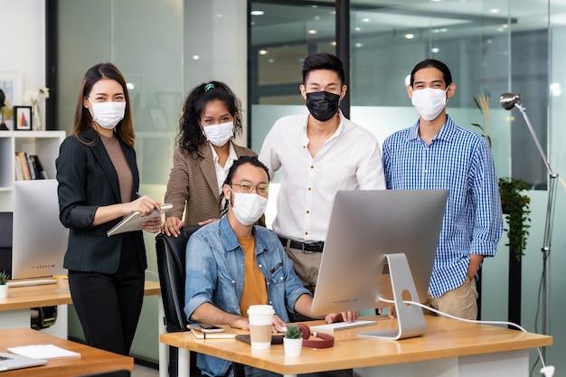 Азиатские деловые люди, работающие в офисе в защитной маске