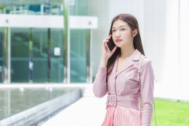 ピンクのドレスを着たアジアのビジネス専門家は、建物の誰かと真剣に電話をかけています